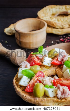 Italian dried bread Friselle on wooden board with tomatoes cherry, cheese mozzarella, olives, tuna, basil and pepper. Italian food. Healthy vegetarian food. Selective focus. - stock photo