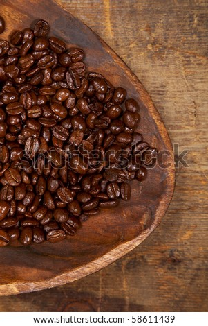 italian espresso blend coffee beans in handmade wood bowl on old wooden table, shallow dof - stock photo
