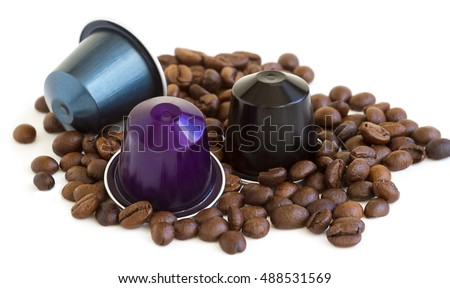 Italian espresso coffee capsules or coffee pods with some roasted coffee beans on white isolated background