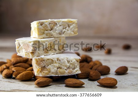 Italian festive torrone or nougat and almonds on a rustic wooden table, copy space, close up with selected focus, very narrow depth of field - stock photo