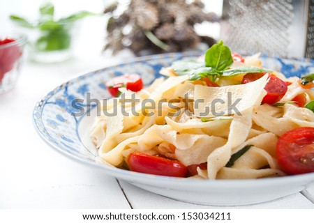Italian fettuccine pasta with cherry tomatoes and parmesan - stock photo