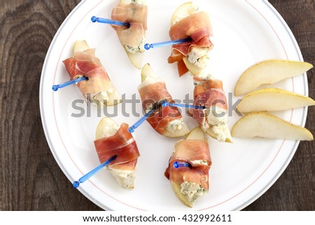 Italian finger food, prosciutto with blue cheese and pear.