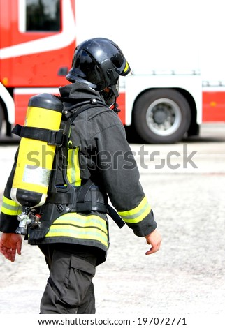 Italian firefighter with the oxygen cylinder and the helmet walks towards the fire - stock photo
