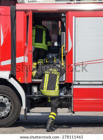 Italian firefighters climb on the trucks of firefighters during an emergency - stock photo