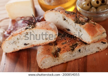 Italian focaccia bread with olives, rosemary and olive oil - stock photo