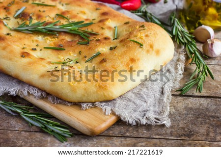 Italian focaccia bread with rosemary and garlic on a rustic background, selective focus - stock photo
