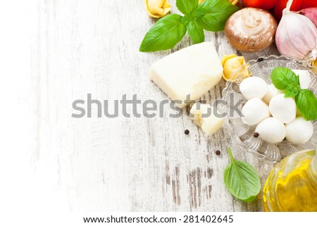 Italian food background, with basil, tortellini, mushrooms, parmesan, mozzarella balls, olive oil, garlic, peppercorns on vintage white wooden table. Background with copy space. - stock photo