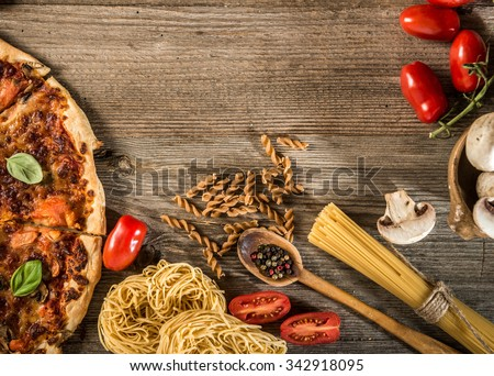 Italian food background with pizza, raw pasta and vegetables on wooden table