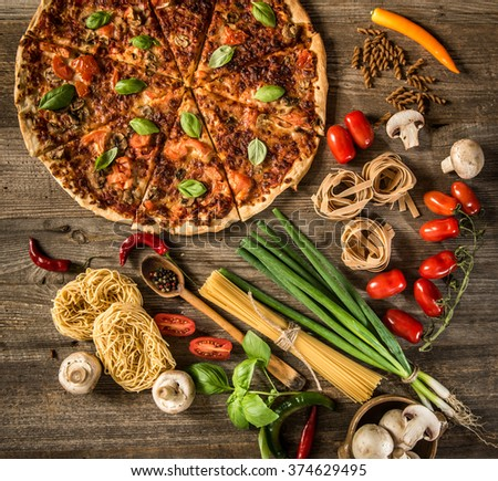 Italian food background with pizza, raw pasta and vegetables on wooden table - stock photo
