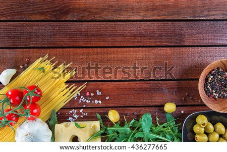 Italian food background, with spaghetti, arugula, herbs, fresh cheery baby tomatoes, olives, emmental cheese, spices, on wooden background. - stock photo