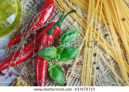 Italian food background, with  tomatoes, basil, spaghetti, olive oil, peppercorns, chili pepper and thyme. Food concept. - stock photo