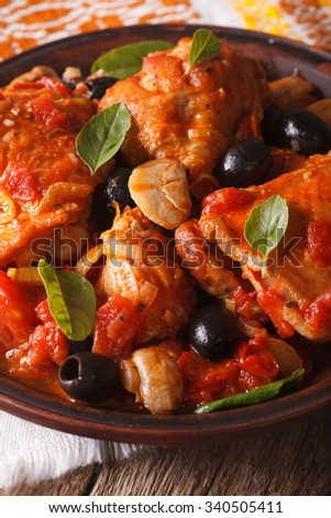 Italian food: Chicken Cacciatori with basil on a plate close-up. Vertical
