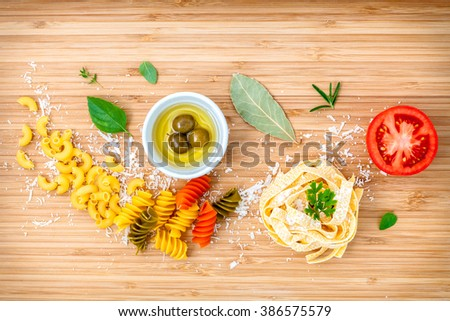 Italian food concept pasta with vegetables olive oil and spices herbs parsley , basil ,bay leaves and rosemary set up with white cheese on wooden background. - stock photo