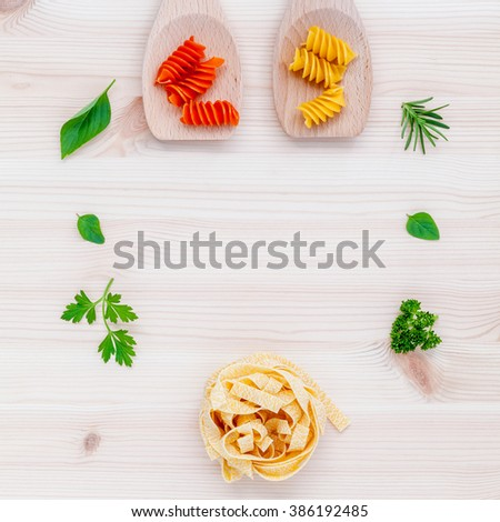 Italian food concept pasta with vegetables olive oil  with spices herbs sage,parsley holy basil and basil set up with wooden background. - stock photo