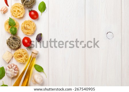 Italian food cooking ingredients. Pasta, tomatoes, basil. Top view with copy space - stock photo