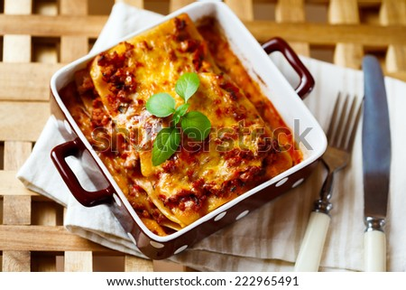 Italian Food. Hot tasty Lasagna plate served with fresh basil leaf on wooden table. Top view. - stock photo