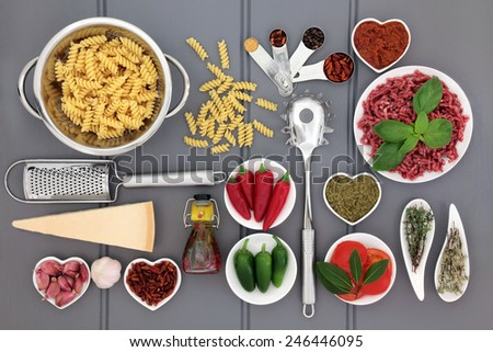 Italian food ingredients and kitchenware over wooden grey background. - stock photo