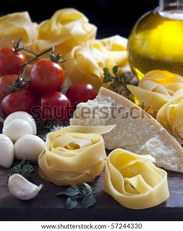 Italian food ingredients, including pasta, mozzarella, tomatoes, parmesan, olive oil, garlic and herbs.  Lovely pappardelle in the making. - stock photo