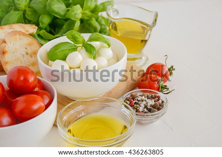 Italian food ingredients â?? mozzarella, tomatoes, basil and olive oil on white background, selective focus, copy space - stock photo