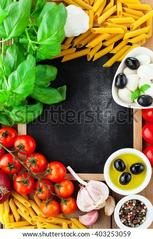 Italian food ingredients - tomatoes, basil, olives, olive oil, garlic, peppercorns and mozzarella on rustic wooden background, with chalkboard. Top view - stock photo