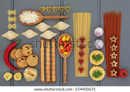 Italian food ingredients with pasta, herb and spice selection, over grey wooden background. - stock photo