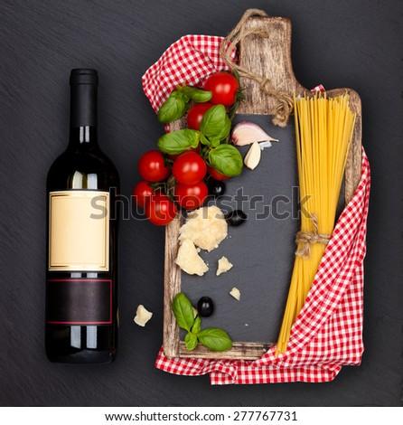 Italian Food. Italian pasta ingredients and bottle of wine on black slate board. - stock photo