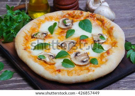 Italian food. Mediterranean cuisine. Delicious pizza with mushrooms and basil - thin pastry crust on wooden background. - stock photo