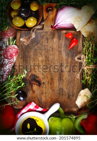Italian food. Old cutting board  surrounded by fresh food ingredients. Toned photo.  Vintage style. - stock photo