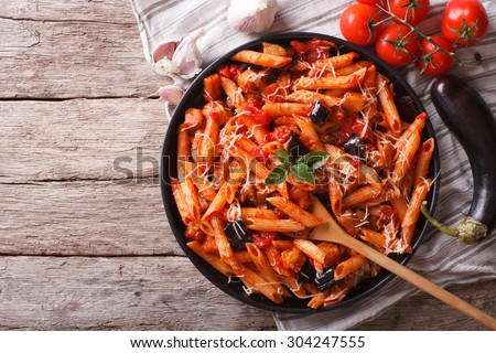 Italian food: Pasta alla Norma close-up on the table and ingredients. horizontal top view - stock photo
