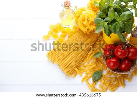 Italian food pasta ingredients,basil,tomato,olive oil on white wooden background - stock photo