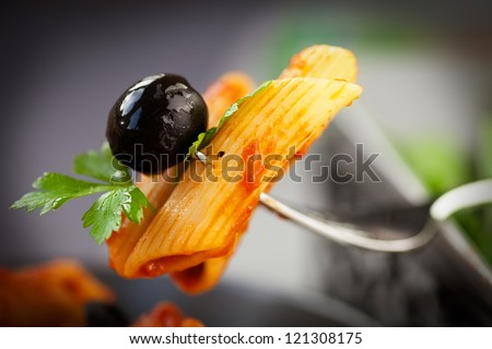Italian food. Pasta penne with tomato sauce, olives and garnish - stock photo