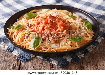 Italian food: pasta with Amatriciana Sauce, cheese and basil close-up on a plate on the table. horizontal