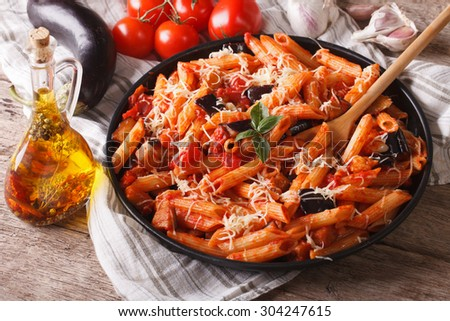 Italian food: Penne with eggplant and tomatoes close-up on the table and ingredients. horizontal - stock photo