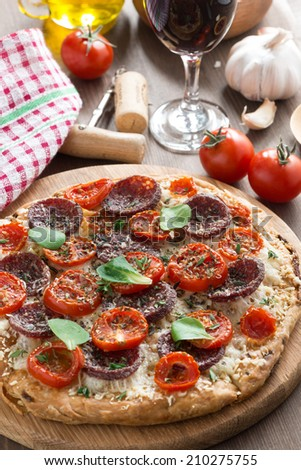 Italian food - pizza with salami and tomatoes, glass of wine, vertical - stock photo