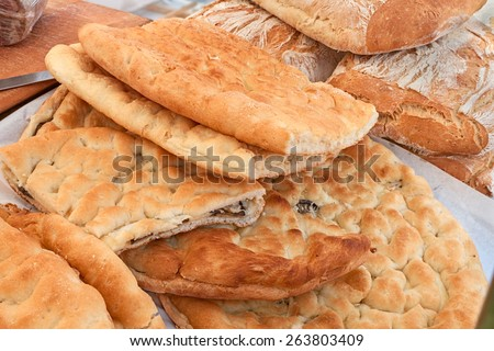 Italian food: traditional focaccia of Tuscany, a flat oven-baked bread product with olive oil. Similar to pizza doughs but more soft, very popular in Italy, can be stuffed with vegetables or meat  - stock photo