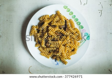 italian fusilli pasta with mushrooms, garlic and pepper, isolated on the table - stock photo