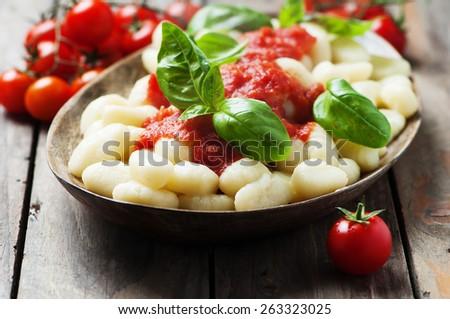 Italian gnocchi with tomato and basil, selective focus - stock photo