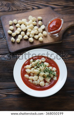 Italian gnocchi with tomato sauce in a rustic wooden setting - stock photo