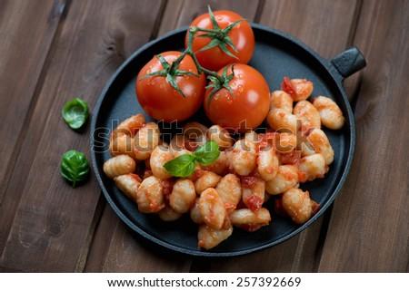 Italian gnocchi with tomato sauce on a dark wooden background - stock photo