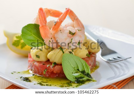 Italian gnocci and tiger prawns on tomato ragout with basil - stock photo
