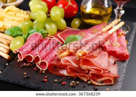 italian grissini stick bread with prosciutto ham  on black board with appetizers - stock photo