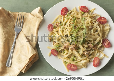 Italian health conscious fettuccine alfredo with halved cherry tomatoes and arugula garnish - stock photo