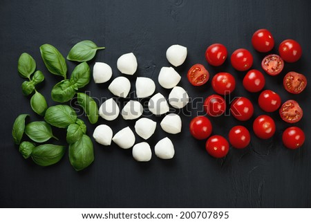 Italian ingredients of green basil, red tomatoes and mozzarella - stock photo