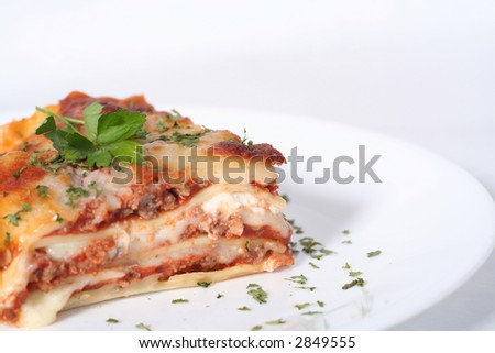 Italian lasagna garnished with parsley on a white plate against a white background - stock photo