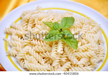 Italian macaroni with original ingredients, on golden fabric - stock photo