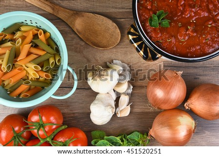 Italian meal ingredients on a wood kitchen table. A pot of sauce, colander of rigatoni, tomatoes, garlic, oregano, and onions seen from a high angle.  - stock photo