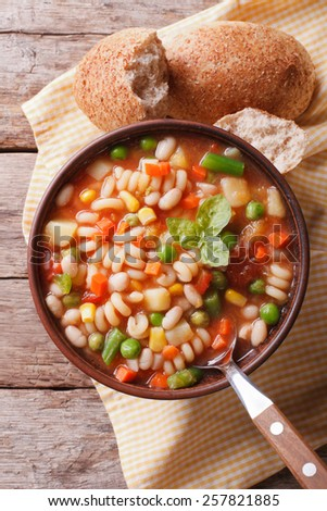 Italian minestrone soup and bread on the table. Vertical view from above  - stock photo