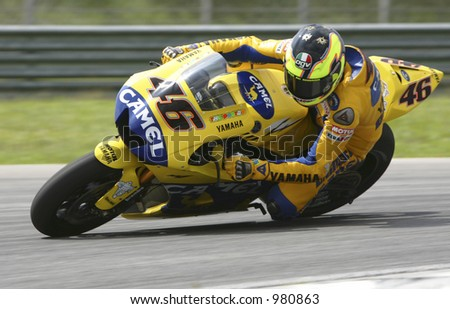 Italian MotoGP roder Valentino Rossi takes a corner during a 2006 pre-season test at Sepang International Circuit, Malaysia. - stock photo