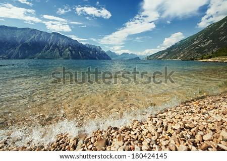 Italian mountain Garda lake with pebble beach in summer - stock photo