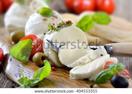 Italian mozzarella cheese snack with cherry tomatoes, basil and olives served on a wooden board with toast bread - stock photo